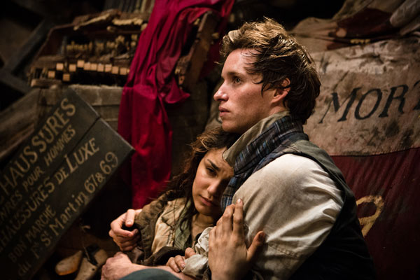 Marius (Eddie Redmayne) holds Eponine (Samantha Barks) behind the barricade as the fight rages on.