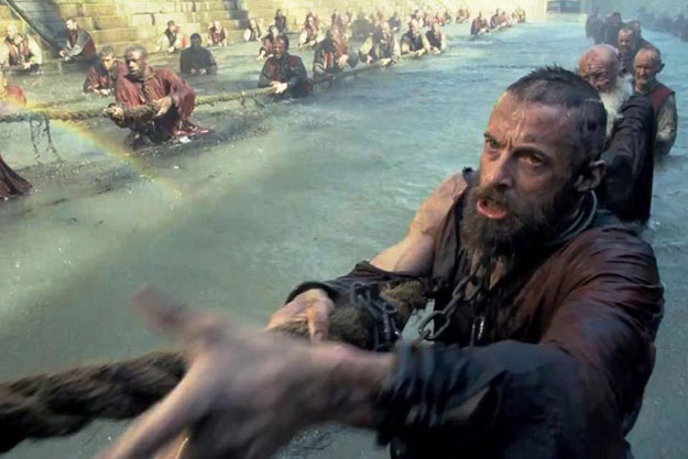 Hugh Jackman works the docks as the convict Jean Valjean in the 2012 film's opening sequence.